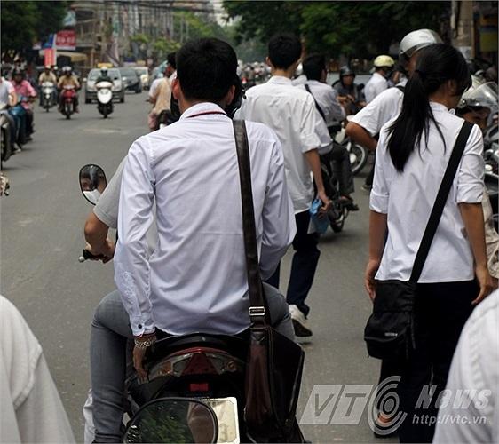 Bước ra khỏi trường thi, nam sinh này bước vội lên xe, trong khi phụ huynh cũng không nhắc nhở con em mình đội mũ bảo hiểm.