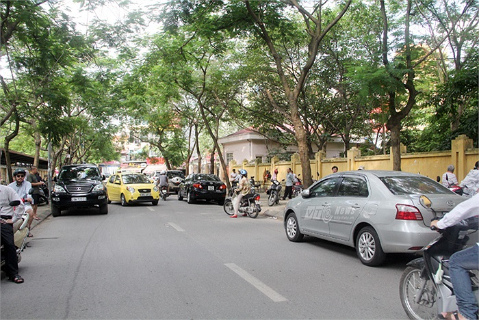 Trước mỗi buổi thi hay sau khi kết thúc thời gian làm bài các môn thi tốt nghiệp, tại các cổng trường thi tại Hà Nội không hiếm gặp hình ảnh những dãy dài ô tô chờ đón con (Phạm Thịnh)