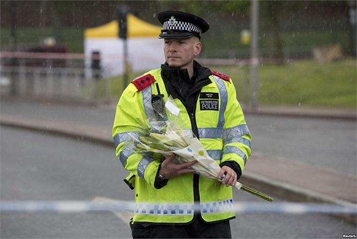 Cảnh sát mang hoa tới gần nơi binh sĩ Anh bị giết tại khu Woolwich, thủ đô London