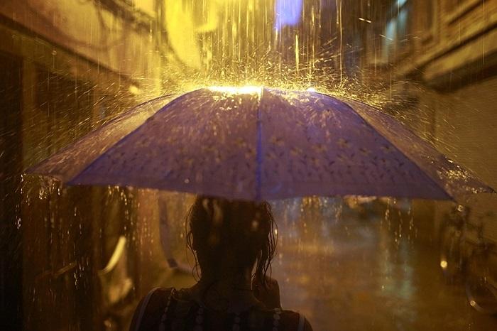 Cô gái đi bộ trong cơn mưa nặng hạt ở Katmandu, Nepal