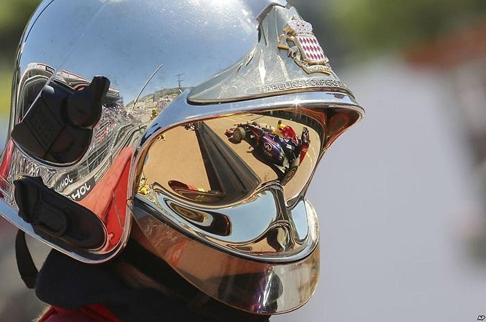 Xe của tay đua Sebastian Vettrel người Đức phản chiếu trên mũ bảo hiểm của nhân viên cứu hỏa tại buổi chạy thử cho giải F1 ở Monaco