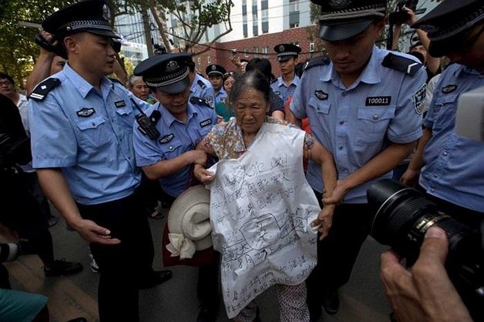 Một bà cụ biểu tình ủng hộ cựu chính trị gia Bạc Hy Lai bên ngoài tòa án sáng 22/8