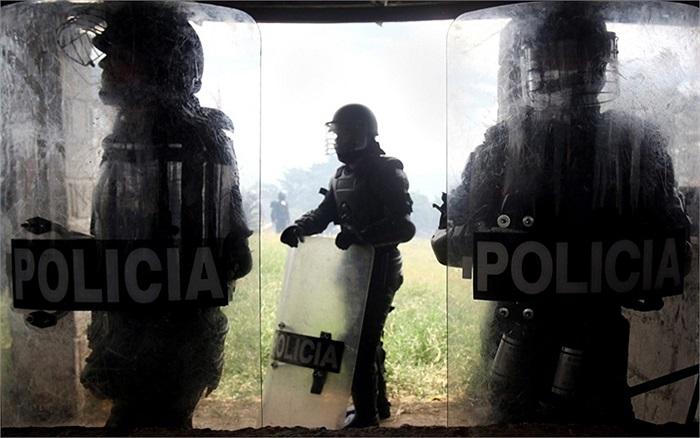 Các thành viên của quân đội Colombia chờ đợi sau khi có cuộc đụng độ với nông dân trên một con đường ở tỉnh Cauca, phía tây nam Colombia