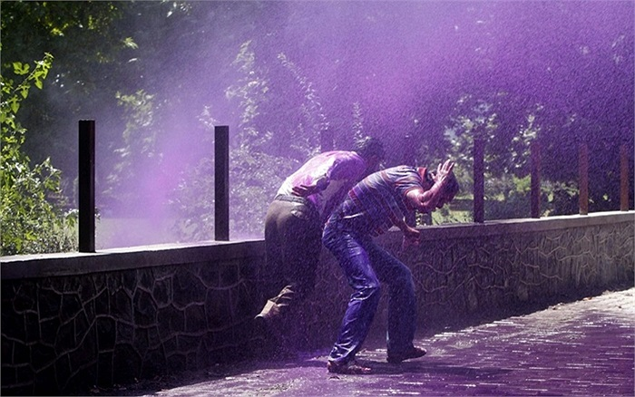 Nhân viên chính phủ Kashmir phun nước màu trong lúc cảnh sát giải tán người dân trong một cuộc biểu tình ở Srinagar, Ấn Độ