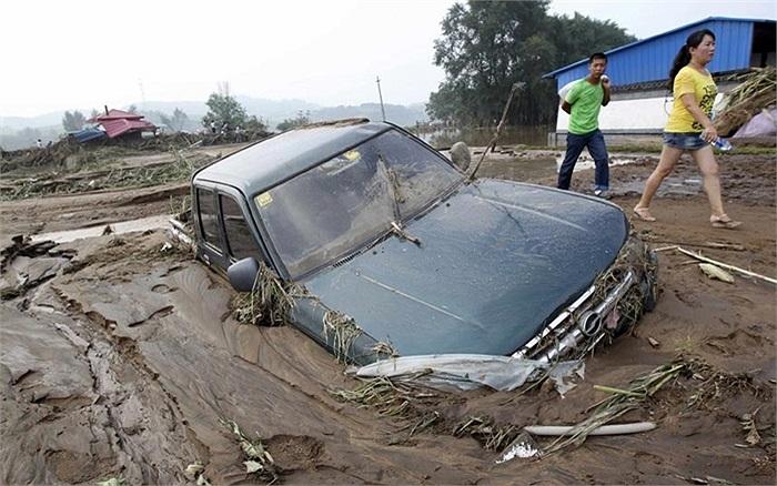 Người dân đi bộ qua chiếc xe bị mắc kẹt trong bùn sau một trận mưa lớn trút xuống Phủ Thuận, Liêu Ninh, Trung Quốc