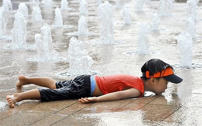 Cậu bé nằm xuống đài phun nước để làm mát trong những ngày nắng nóng cao độ ở trung tâm Seoul, Hàn Quốc