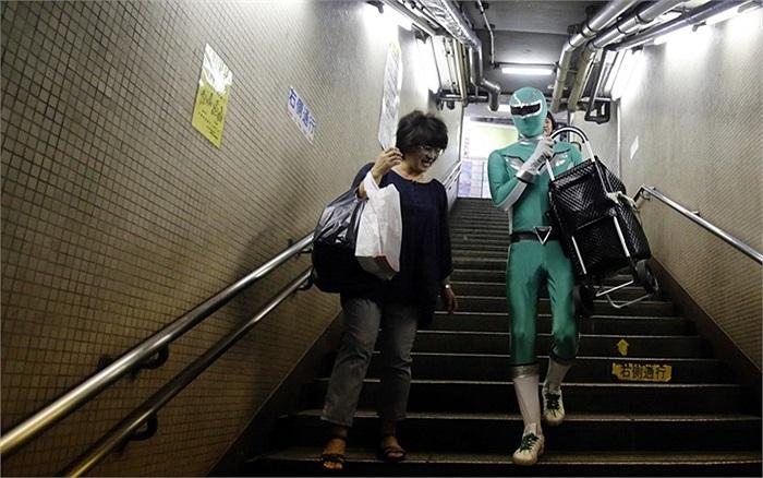 Tadahiro Kanemasu mặc trang phục siêu nhân giúp đỡ hành khách xuống một ga tàu điện ngầm ở Tokyo, Nhật Bản