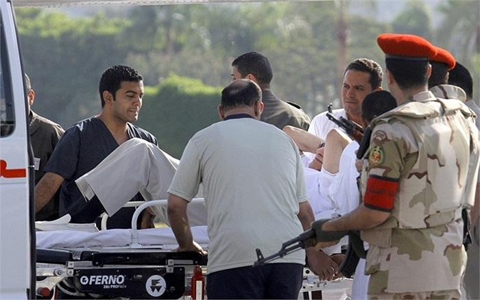 Nhân viên y tế và cảnh sát hộ tống cựu Tổng thống Hosni Mubarak của Ai Cập lên xe cứu thương đến bệnh viên sau khi ông được trả tự do