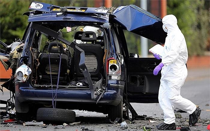 Chuyên gia bom mìn kiểm tra phần còn lại của chiếc xe sau khi nó nổ tung trên đường Hillview ở Belfast, Ireland