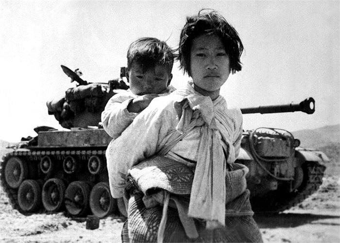 Cô gái Triều Tiên cõng đứa em trai lững thững đi qua một chiếc xe tăng M-26 tại Haengju, Hàn Quốc, ngày 9/6/1951. Ảnh: Hải quân Mỹ