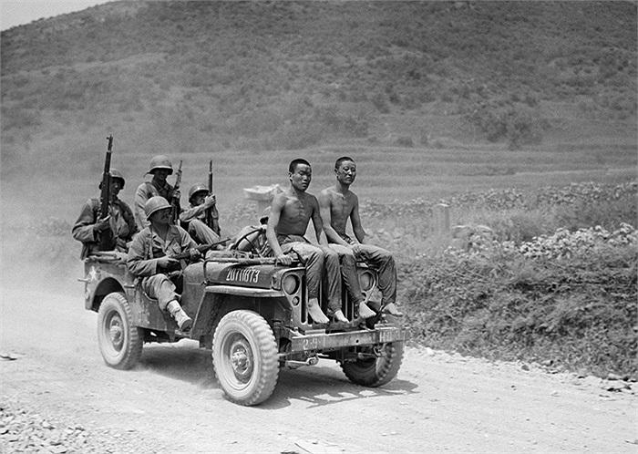 Hai tù nhân Bắc Triều Tiên bị bắt trong cuộc chiến tại Yongsan ngày 2/9/1950 ngồi trên mui xe jeep dưới sự giám sát của lính Mỹ thuộc Sư đoàn bộ binh số 2. Ảnh: AP