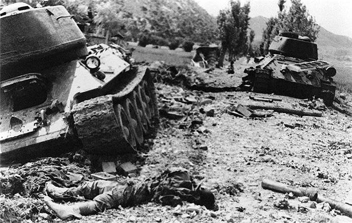 Thi thể một lính xe tăng của miền Bắc nằm trên mặt đất (phía dưới bên trái) sau khi xe tăng của anh bị bắn trong cuộc tấn công quân Hàn Quốc tại Indong, Bắc Waegwan, ngày 13/8/1950. Ảnh: AP