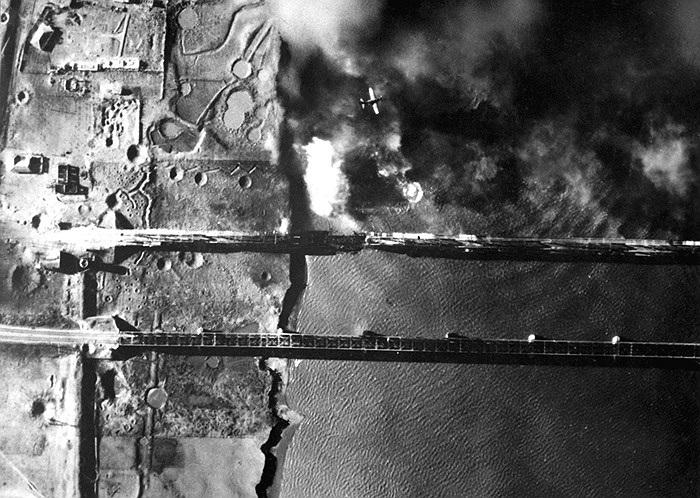 Máy bay AD-3 của hải quân Mỹ (chính giữa, phía trên bức ảnh) rút lui sau khi vừa bổ nhào để thả một quả bom 2.000 cân Anh vào đầu cầu phía Triều Tiên của cây cầu bắc qua sông Áp Lục ở Sinuiju, Mãn Châu Lý vào ngày 15/11/1950. Ảnh: Bộ Quốc phòng Mỹ