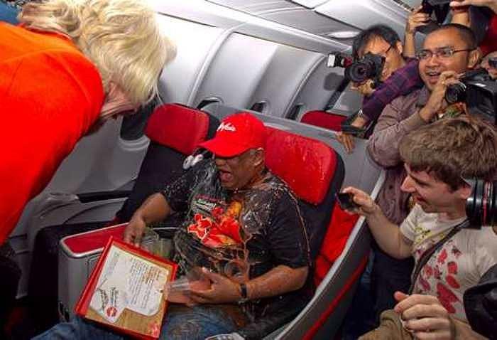 Ông Branson phục vụ các đồ ăn, thức uống cho khách tận tình như những tiếp viên hàng không khác. Tỷ phú người Anh thậm chí còn làm đổ nước lên người ông Fernandes để đùa.