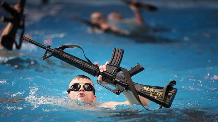 Bài học tiếp theo là bơi và giữ một khẩu súng M16 bằng cao su - có trọng lượng như súng thật nổi trên mặt nước