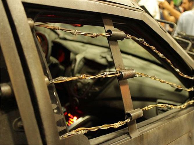 Cửa sổ xe được bảo vệ bằng sắt tấm và lưới sắt.