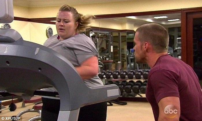 Trong ảnh là người hướng dẫn tập luyện, anh Chris, đang hỗ trợ chị Ashley thực hiện các bài tập giảm cân.