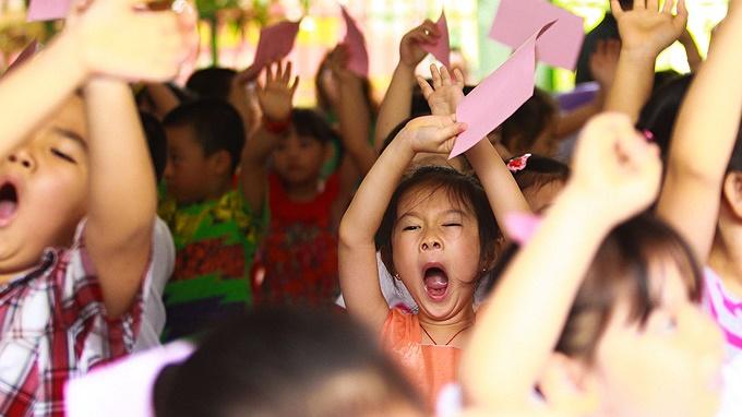 Trước khi vào phòng thi, các bé được thầy cô trong trường tập thể dục vận động để bớt căng thẳng. Tuy nhiên nhiều bé ngáp ngắn ngáp dài và bỡ ngỡ vì đây là lần đầu tiên các em bước vào một kỳ thi.