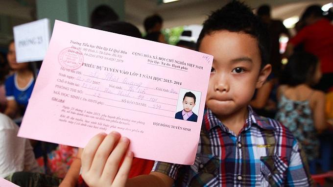 Bé Lê Nhật Quang, 6 tuổi, cầm trên tay phiếu dự tuyển vào lớp 1 năm học 2013-2014 tại Trường tiểu học dân lập Lê Quý Đôn.