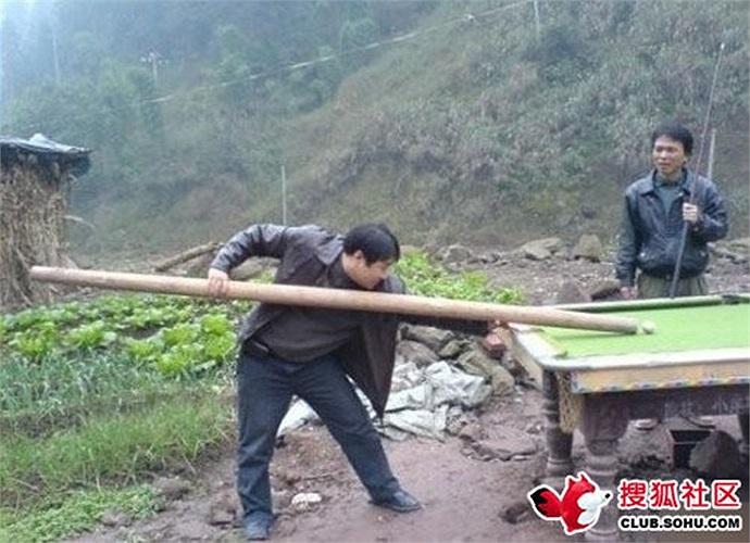 Một người đàn ông cầm cây gỗ to làm gậy chơi bi-a