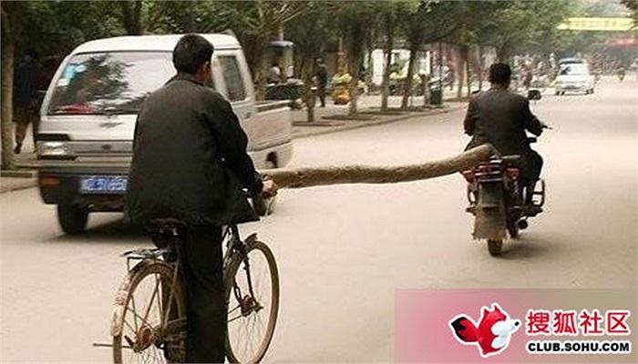 Chiếc xe máy dùng cây gỗ dài làm cầu nối kéo xe đạp thật quá mạo hiểm