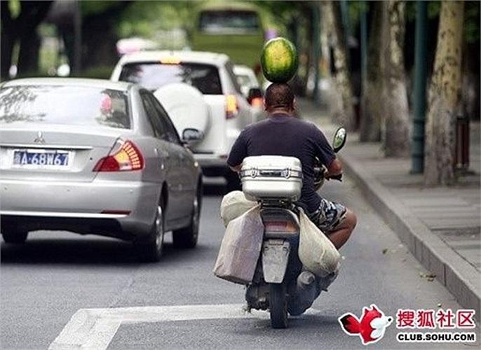 Người đàn ông di chuyển bình thường với quả dưa hấu trên đầu
