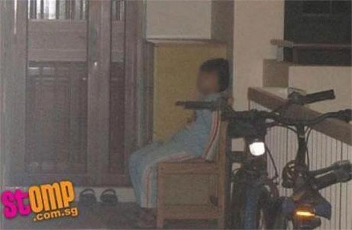 Một bé trai trong bộ đồ ngủ đã bị người thân đuổi ra khỏi nhà, bắt phải ngủ trên chiếc ghế nhỏ, co ro trong thời tiết lạnh khi đồng hồ điểm 10 giờ tối.