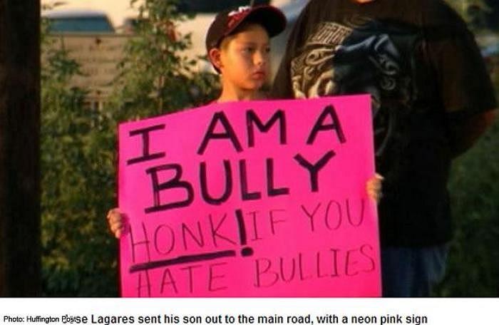Một học sinh tiểu học với thói ăn hiếp bạn bè đã bị phụ huynh bắt đứng ngoài đường và giơ một tấm bảng 'tôi là kẻ bạo hành'.