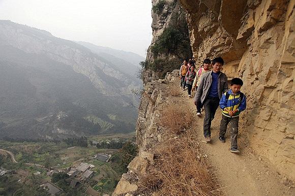 Giáo viên Xu Liangfan, 37 tuổi, hộ tống học sinh đi trên con đường vách đá cheo leo