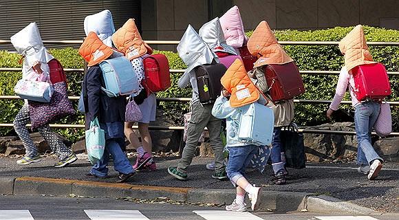 Các bạn trường tiểu học ở Tokyo đội mũ bảo hộ tới trường sau trận sóng thần năm 2011