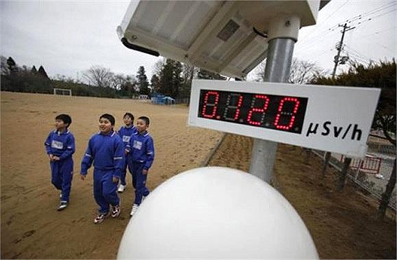 Học sinh Nhật Bản đi bộ gần đồng hồ đo độ phóng xạ, cách nhà máy điện hạt nhân Fukushima, Daiichi 13 dặm