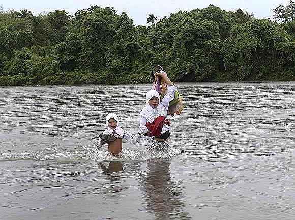 Các học sinh thuộc 46 gia đình trong một ngôi làng tại Indonesia lội qua sông đi học