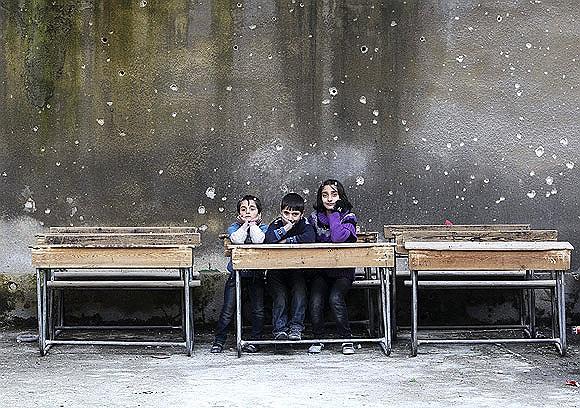 Các em học sinh ngồi trên ghế tại trường Al Tawheed trong cuộc nội chiến Syria