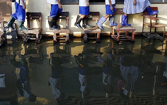 Vì một trường tiểu học thuộc tỉnh Rizal phía Bắc Manila không có hệ thống thoát nước nên học sinh phải đi ủng và trèo ghế đến lớp
