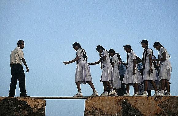 Nữ sinh trung học phải trèo qua một tấm ván nối giữa các pháo đài từ thế kỷ 16 ở Sri Lanka