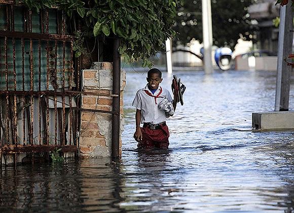 Một học sinh đi học trên đường phố ngập nước ở Hanava, Cuba