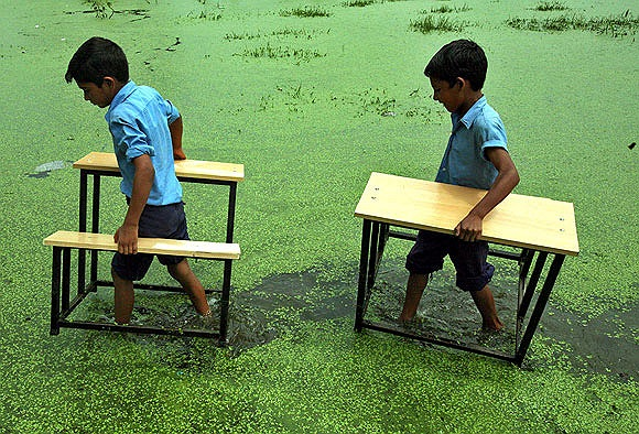 Học sinh vác bàn ghế sau khi mưa lụt tại làng Bassi Kalan, Ấn Độ năm 2011
