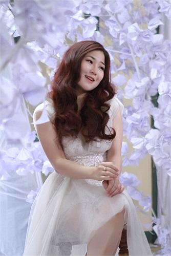 Hương Tràm đã chọn một chiếc đầm trắng cùng kiểu trang điểm và làm tóc nhẹ nhàng để gắn kết với màu sắc và khung cảnh nền nã.