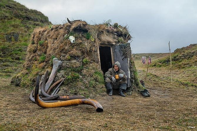 Hình ảnh Milyutin trước cửa lều trên đảo Bolshoy Lyakhovskiy. Túp lều của anh được ngụy trang khéo léo để tránh sự phát hiện của trực thăng biên phòng Nga, những người đã trục xuất hàng chục thợ săn không có giấy phép như anh.
