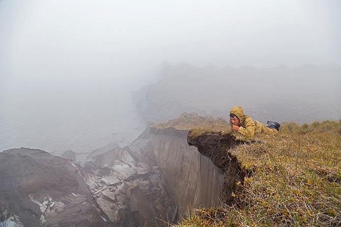 Nằm rạp mình trên mỏm đất nhô cao, Nikolay Haritonov đang chăm chú tìm kiếm ngà voi giữa vùng bờ biển xói mòn và sạt lở.