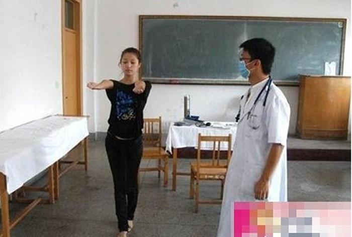 Nhân viên y tế kiếm tra xem hai tay của thí sinh có bị khuyết tật hay không