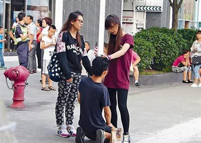 Theo những hình ảnh được cắt ra từ video, chàng trai trẻ đang quỳ xuống trước mặt 2 cô gái ở một con phố đông đúc.