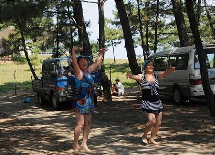 Khách du lịch múa hát dưới bóng cây ở bờ biển phía Đông