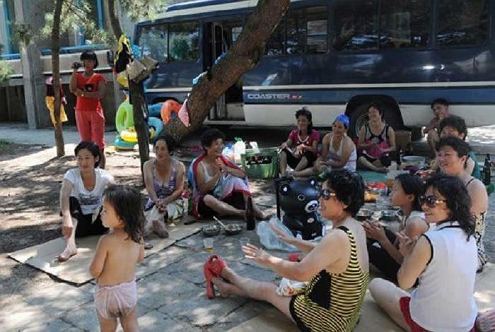 Mọi người ngồi nghỉ dưới bóng cây sau khi tắm biển