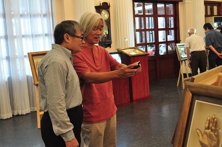 Nhà thơ Nguyễn Duy và nhà phê bình Phạm Xuân Nguyên cùng chụp hình tác phẩm làm lưu niệm