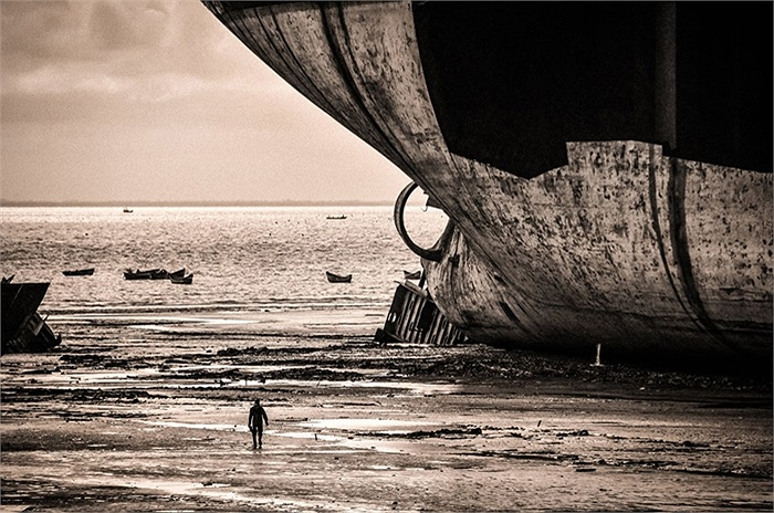Con người bé nhỏ dưới thân của tàu chở dầu khổng lồ trên bờ biển