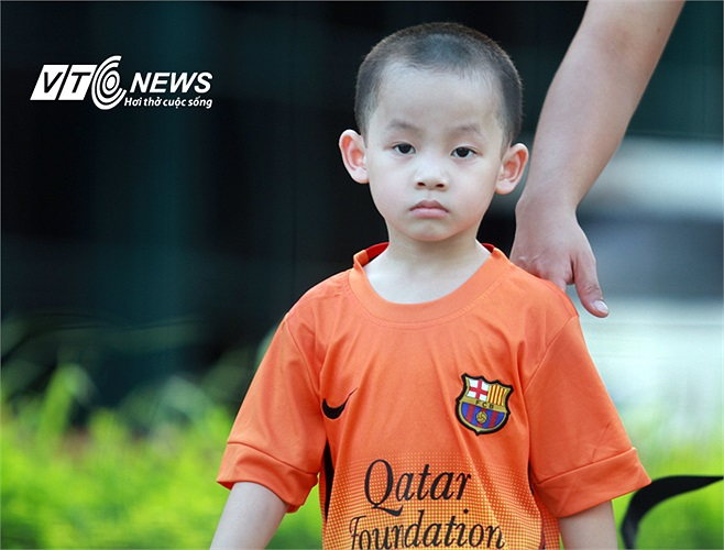 Một cậu bé mặc áo Barca đang cùng bố tới sân tập của U23 Việt Nam.