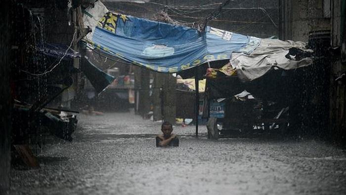 Người đàn ông lội qua con đường ngập đến hơn nửa người ở thủ đô Manila
