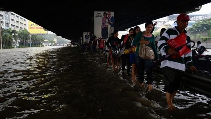 Người dân di chuyển ven đường cao tốc đến điểm không bị lụt