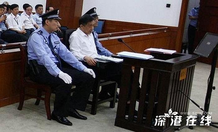 Tại phiên tòa, ông Bạc mặc chiếc áo sơ mi trắng, bên cạnh là hai nhân viên cảnh sát áp tải